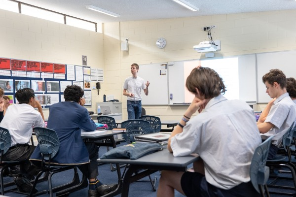 A photo of me lecturing at the Christ Church Grammar School taken by Ben Lim. Seven students are visible.